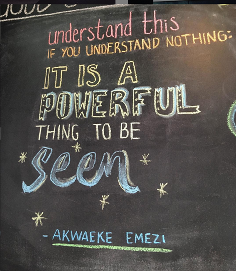 "A quote by Akwaeke Emezi written on chalkboard that reads, ""Understand this if you understand nothing. It is a powerful thing to be seen"""