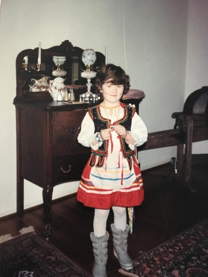 Seven-year-old Amanda wearing a traditional Polish costume and winter boots, and smiling at the camera