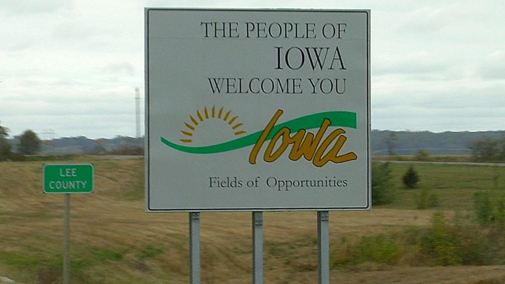 "A ""Welcome to IOWA"" sign on the side of the highway"