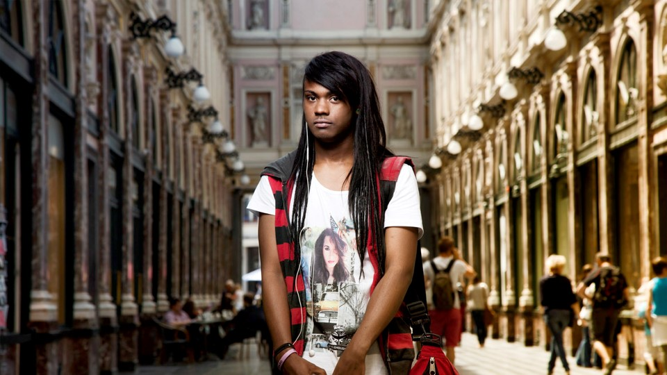 A young queer person of colour stands in a large room looking at the photographer