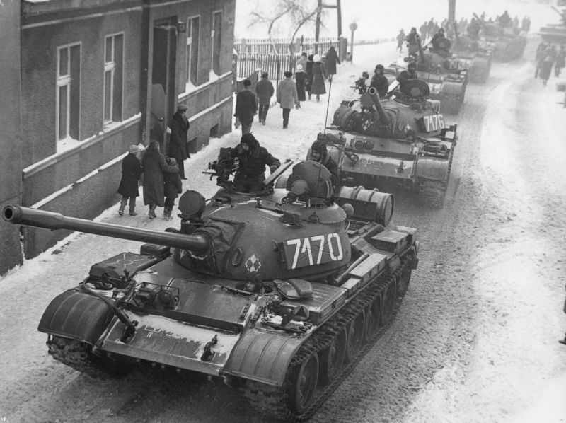 A city street with a line of tanks driving down the road in the snow and people walking on the sidewalks