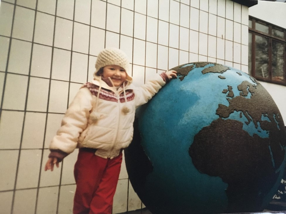Five-year-old Amanda standing beside a large globe