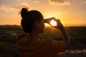 Person looking at a sunset and doing a heart hand sign