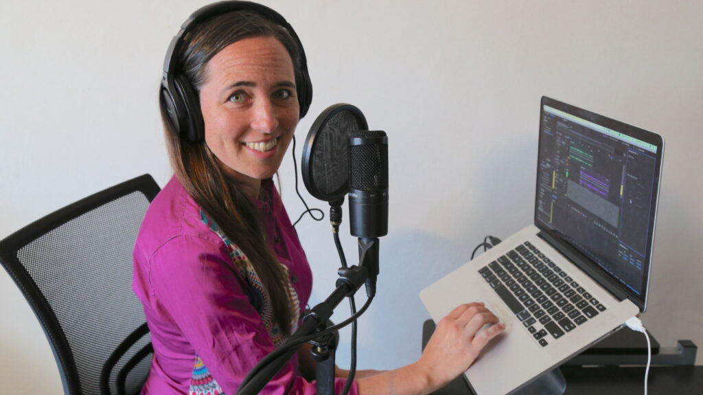 Sarah Van Borek sits with one hand on the keyboard of her laptop, turning and smiling at the camera. A larger microphone sits between the viewer and Sarah, who sports large headphones.