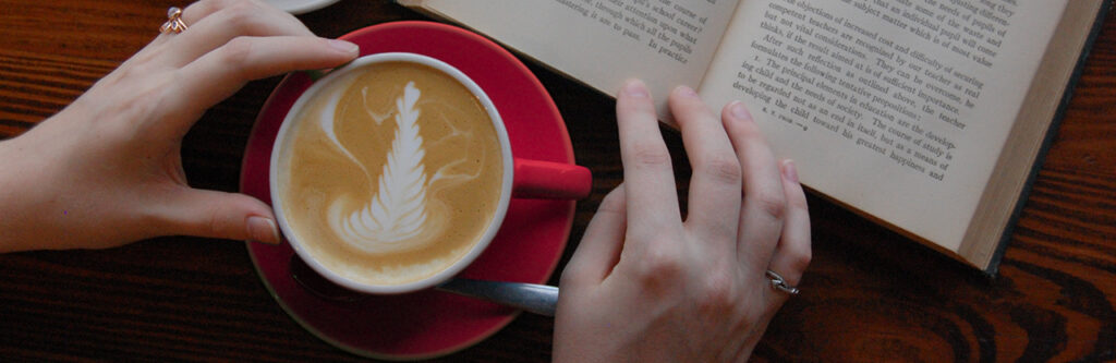 A flatlay of a coffee cup with a book in the corner.