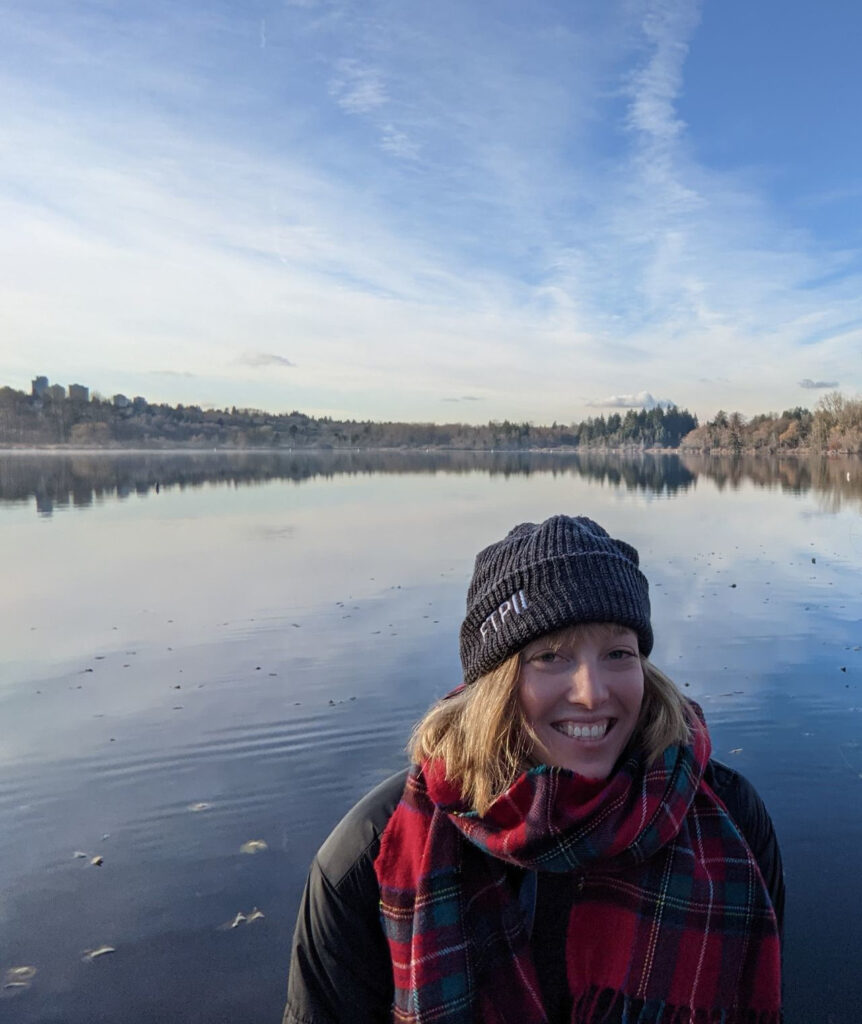Nicola Mulberry smiling in front of a body of water and a blue sky