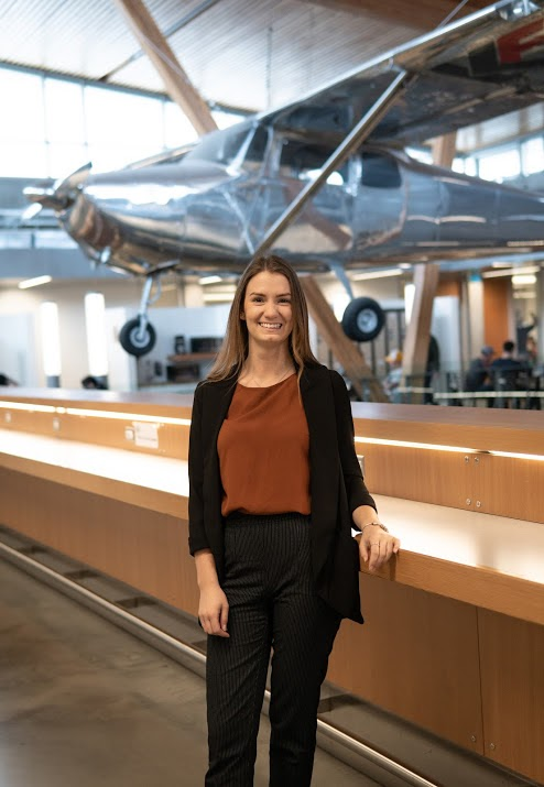 Saige Girouard stands in front of an airplane on display and suspended from the ceiling.