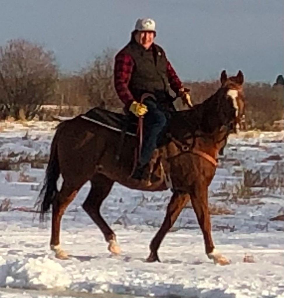 Josh Littlechild riding a horse in a snow covered field