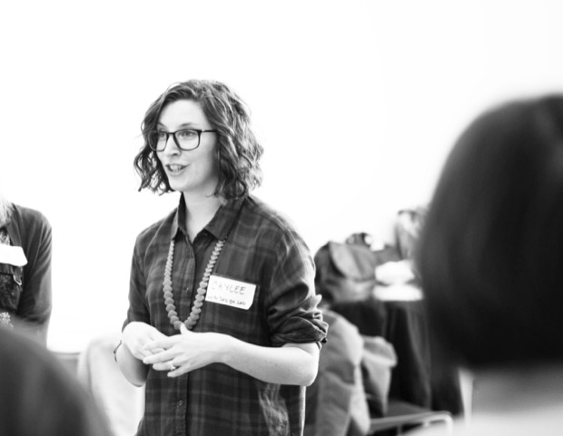 Caylee, sporting glasses, a plaid shirt and name tag, speaks to a group of people