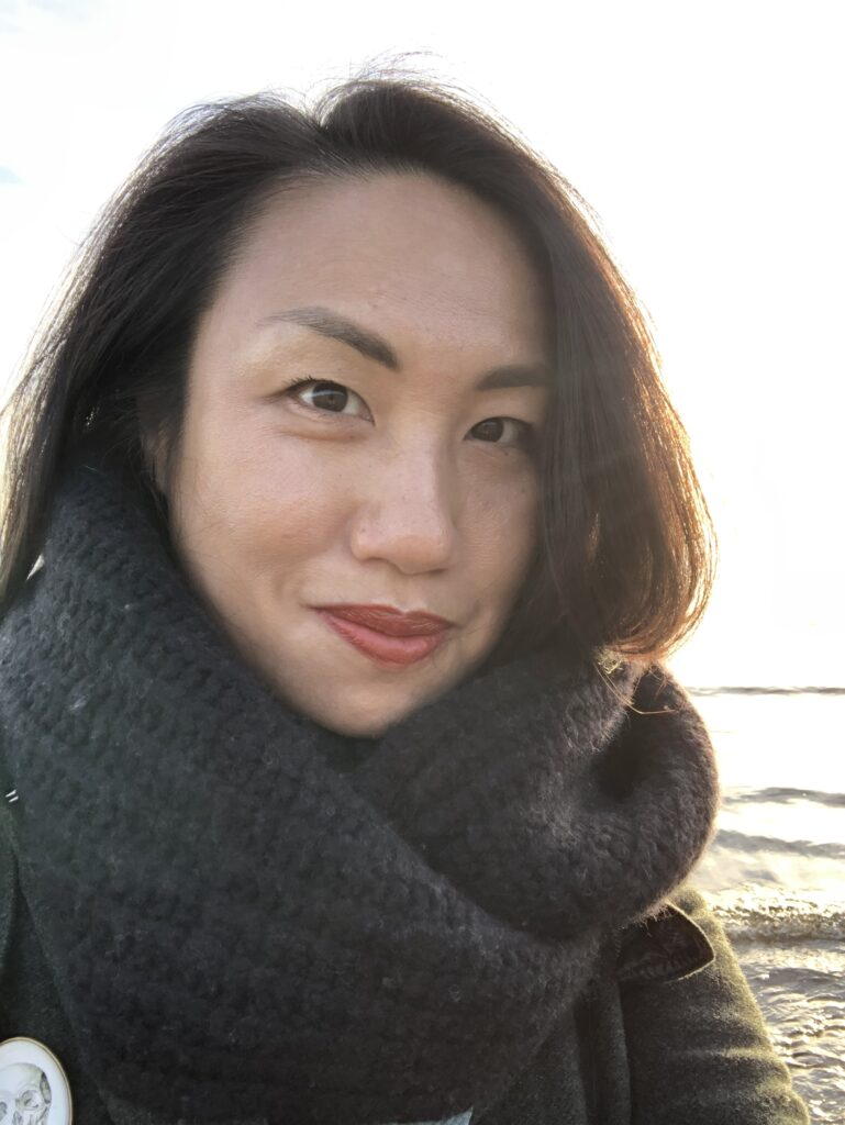 Elle, wrapped in a thick black scarf, smiles on beach