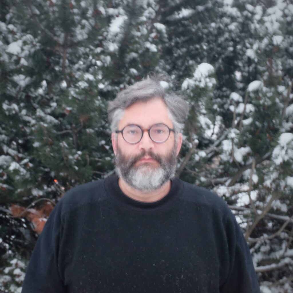 Rob-Roy stands in front of snow-covered trees.