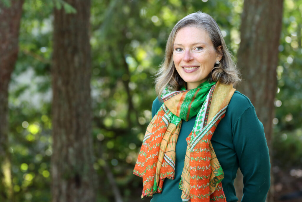 Heather Burke smiles and stands with a forest of trees behind her.